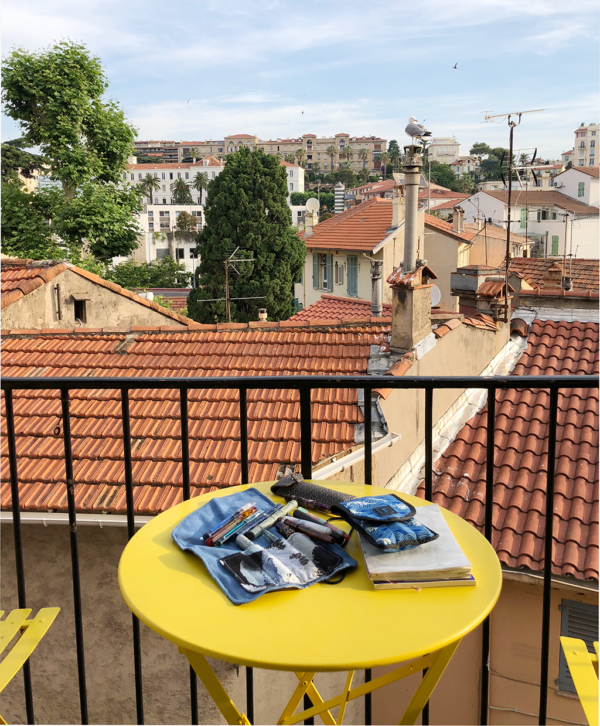 Pens on a yellow table with a view of Cannes