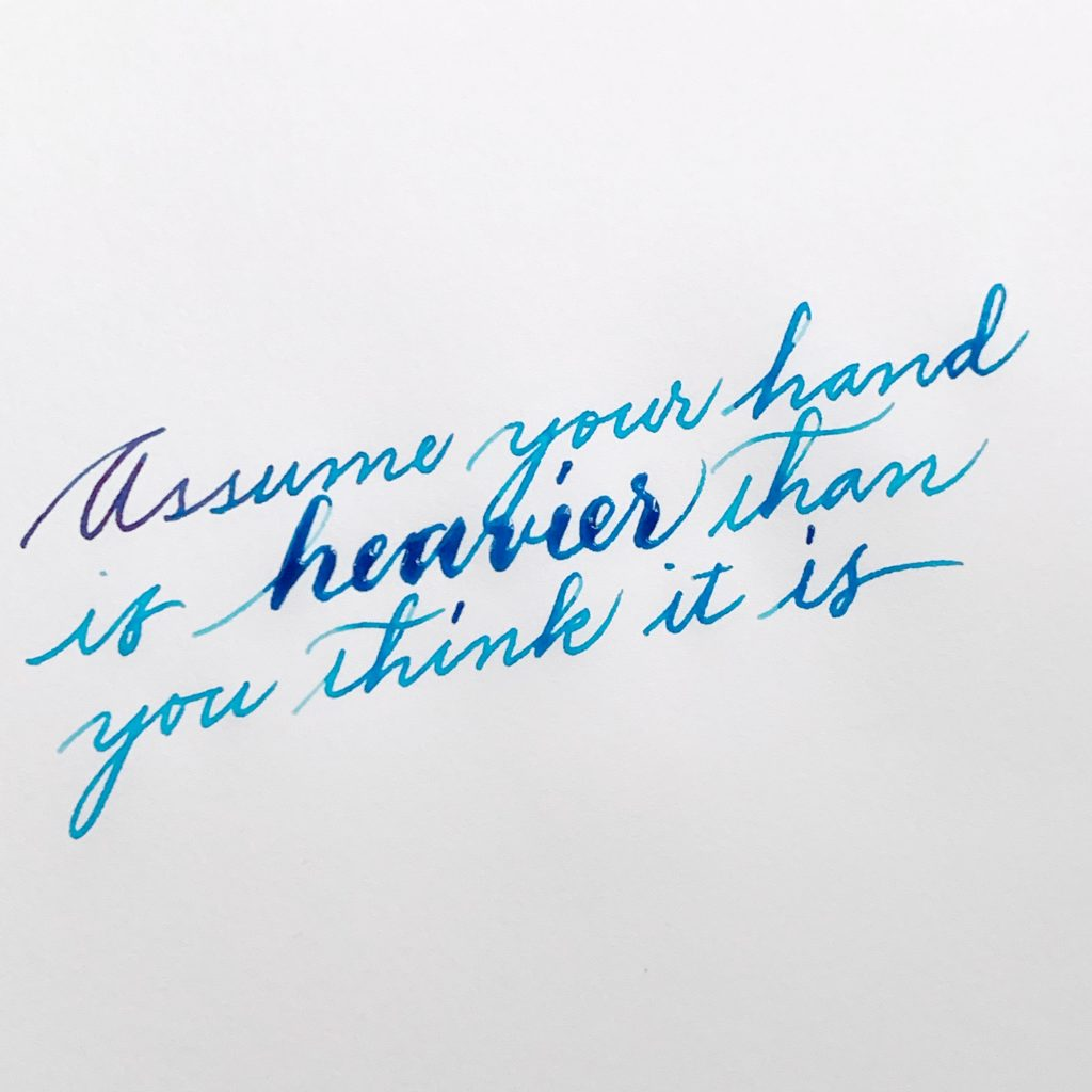 "Written in cursive on paper: ""Assume your hand is heavier than you think it is"""